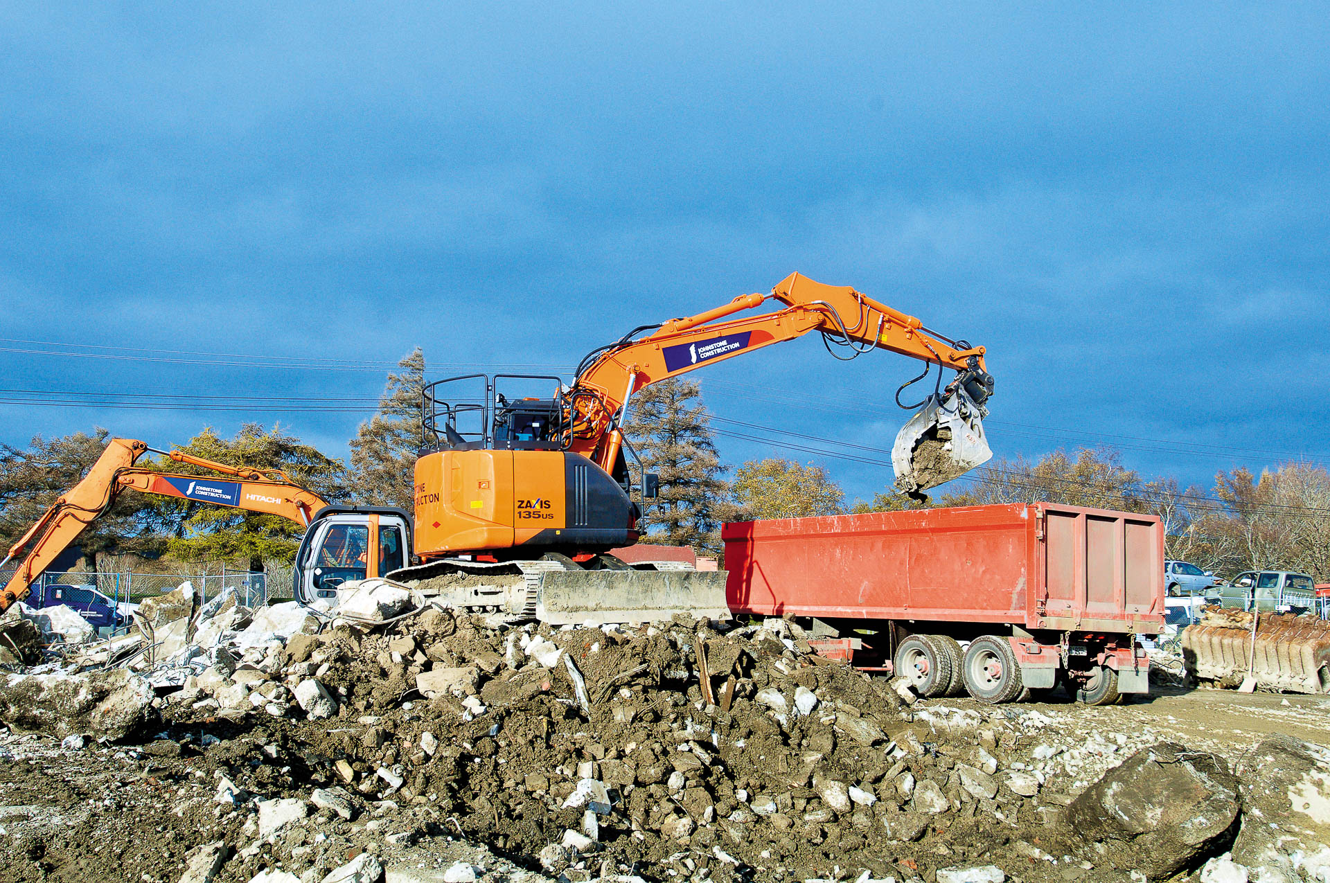 Attach2 Attachments on Hitachi Diggers loading trucks during Demolition